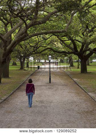 woman walking down tree lined path in Charleston, South Carolina
