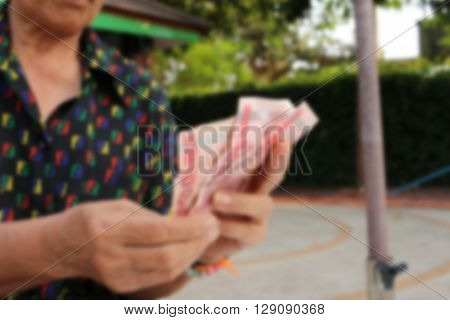 Blurred of woman holding Thailand baht banknotes
