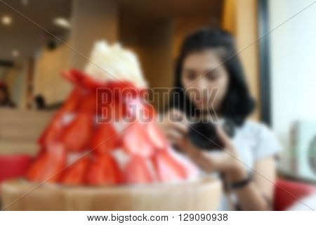 Blurred of woman take a photo of food.