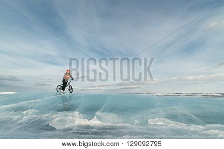 Girl standing on a bmx on the beautiful and dangerous ice.