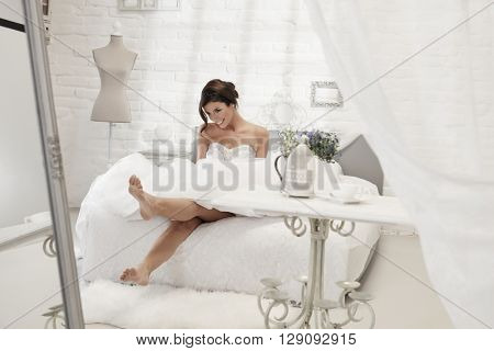 Beautiful happy bride sitting on bed in white bedroom, smiling happy.
