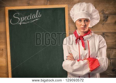 Pretty chef standing with arms crossed against bleached wooden planks background
