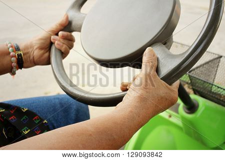 Close up of hands on a steering wheel.