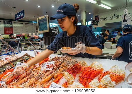 Sydney Australia - November 11 2014: Vendor preparing seafood for a buyer in Famous Sydney Fish Market Sydney New South Wales Australia.