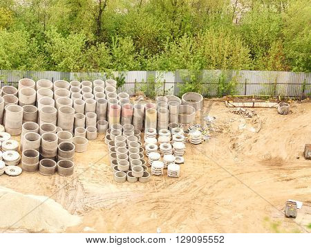 stacks of concrete rings for sewer. of stock vertically stacked concrete drainage pipes construction site view from above