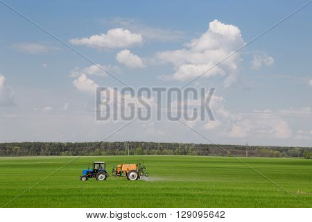 Gomel, Belarus - May 4, 2016: Tractor spraying wheat field with sprayer, herbicides and pesticides.