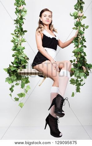 Beautiful young woman dressed as a sexy maid-servant in a skimpy uniform, posing provocatively and swinging on a swing.