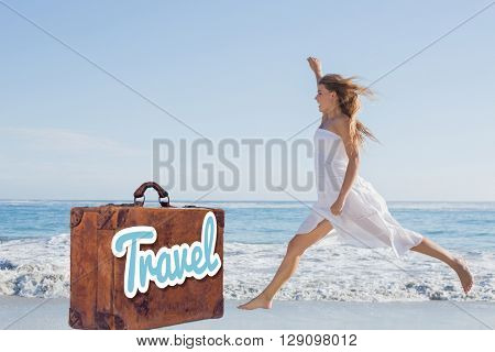 Beautiful blonde in white sundress jumping up on the beach against suitcase with the message travel