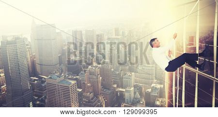 Businessman pulling rope while sitting on cube against image of a city landscape on a sunny day