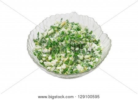 Spring salad with chopped green onions boiled eggs and sour cream in a glass salad bowl on a light background