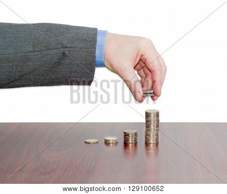 Male hand adds a several coins to the last column of the diagram consisting of columns of euro coins on a wooden table on a light background