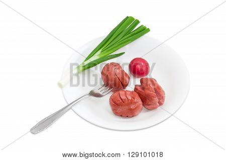 Three short thick fried wieners one of which is on the fork red radish and stalk of green onion on a white dish on a light background