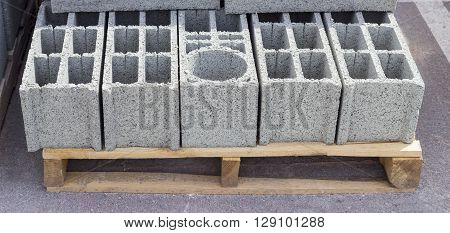 Wall concrete perforated blocks with rectangular and round holes on a pallet on a warehouse