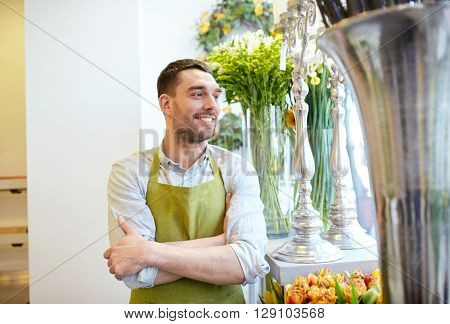 people, sale, retail, business and floristry concept - happy smiling florist man in apron standing at flower shop
