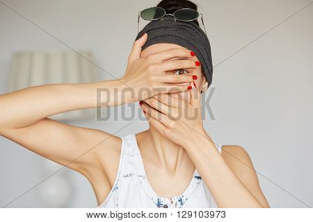 Portrait Of Young Hipster Woman Peeping At The Camera Through Her Fingers. Picture Of Embarrassed Fe
