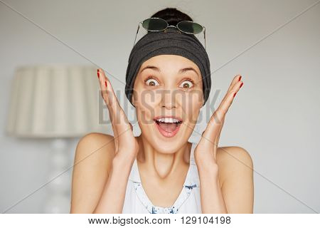 Portrait Of Young Brunette Woman Wearing Headband And Sunglasses On Her Head Screaming With Exciteme