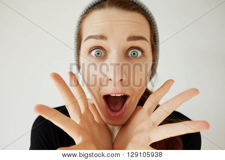 Portrait Of Student Girl Looking And Screaming In Surprise, Mouth Wide Open. Young Female Astonished