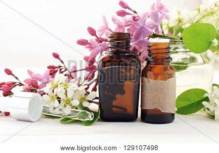 Aromatherapy bottles with essential oils. Fresh blossom. Sweet floral scent.