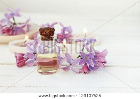 Essential oil in bottle, lilac flowers, tea-candles. Soft focus.