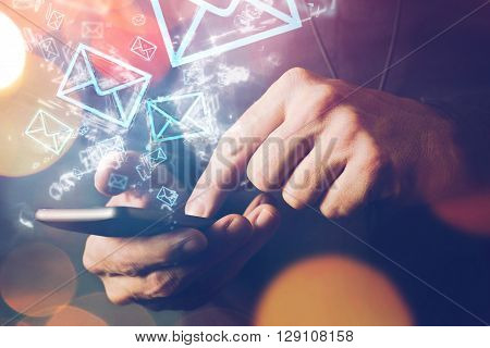 Man sending e-mail message to mailing list contacts using smartphone close up of hands holding phone.