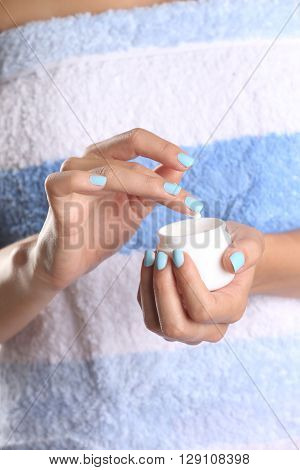 Woman applying cream on hands after shower