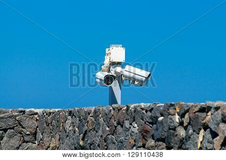 Security camera over a stone wall against the blue sky.