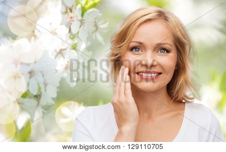 beauty, people and skincare concept - smiling woman in white shirt touching face over natural spring cherry blossom background
