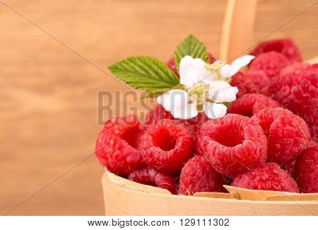 Fresh raspberries in a wooden basket, against rustic wooden background, with copy space