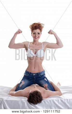 Merry girl shows biceps while sitting astride on guy
