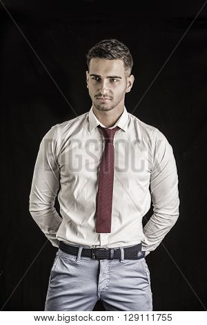 Handsome young man in in white shirt and red neck tie posing on dark background in studio