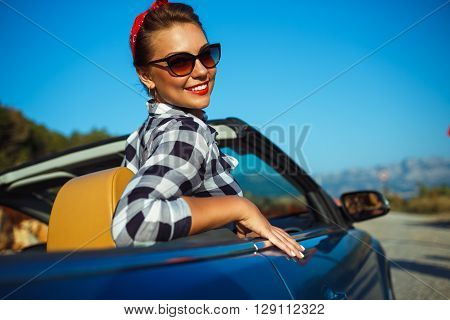Beautiful pin up woman sitting in cabriolet enjoying trip on luxury modern car with open roof fashionable lifestyle concept