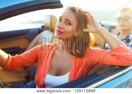 Two young happy girls driving a cabriolet summer vacations concept