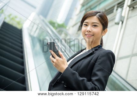 Businesswoman standing on escalator and use of mobile phone