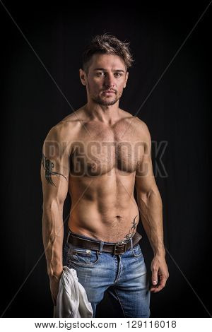 Attractive young man with naked muscular torso, wearing jeans, isolated on black background