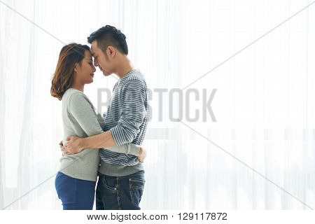 Young Vietnamese couple in love standing and hugging