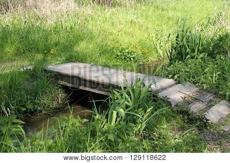 small wooden gangplank across the narrow brook in spring