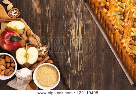 Apple pie with almonds and cinnamon and ingredients over brown wooden table