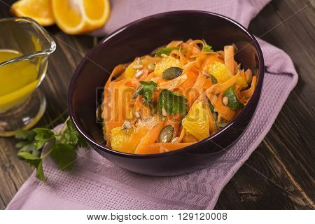 Salad with fresh carrot, orange slices, pumpkin and  sunflower seeds. Selective focus