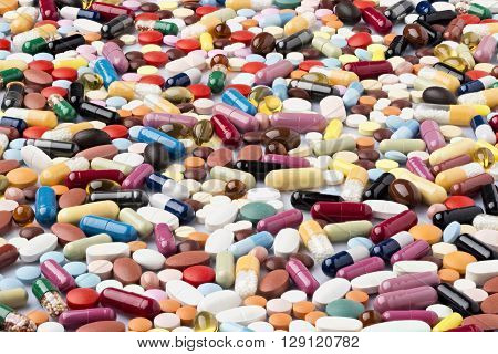 Scattered various colorful medical pills and pharmaceuticals remedy