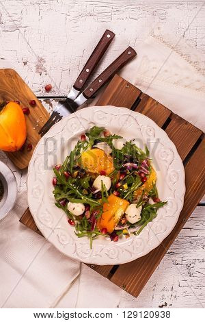 Fresh colorful summer salad with persimmon, arugula, mozzarella  cheese and pomegranate seeds. Top view. Selective focus
