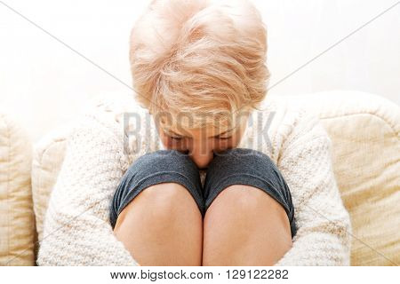 Elderly woman with depression sitting on couch