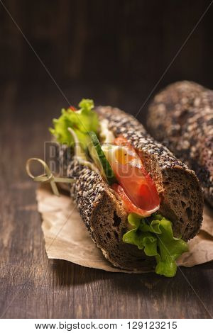 Tasty rye bread sandwhiches with ham, cheese and vegetables over dark wooden table
