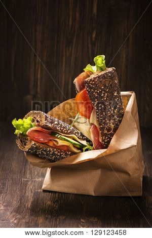 Rye bread sandwiches with ham, cheese and vegetables in a craft paper bag. Take away food. Selective focus