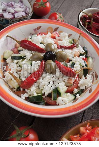 Shopska salad with cheese, vegetables, olives and chili pepper