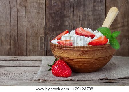 Cottage cheese in clay bowl with strawberries and mint spoon napkin on wooden background. Healthy homemade cottage cheese breakfast or lunch with strawberry sour cream in clay bowl on rustic kitchen table background