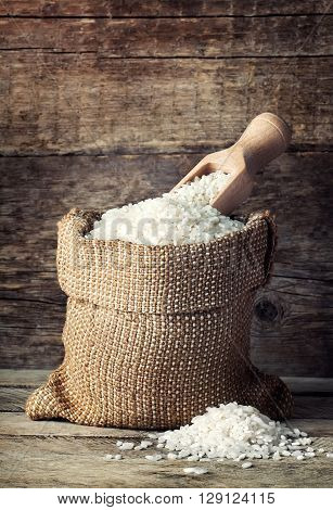 rice in burlap bag with pile of grains on wooden background. White rice on wooden background