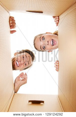 Happy young couple opening a carton box and looking inside