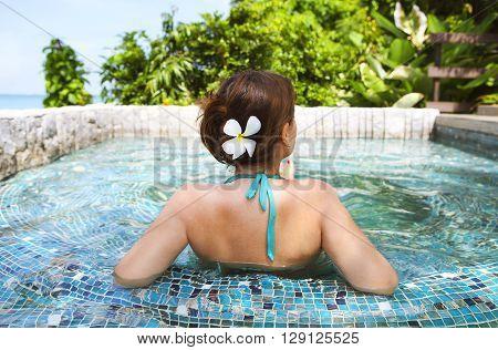 Young beautiful woman relaxing in spa pool. Relaxing serene woman at travel spa resort pool