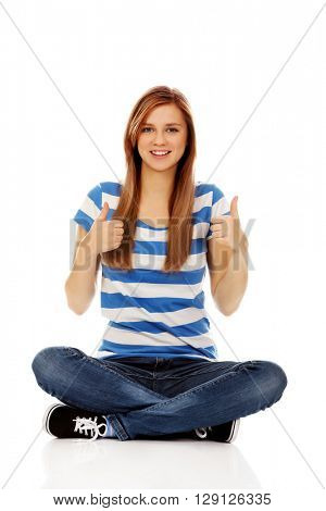 Happy teenage woman sitting with cross legged