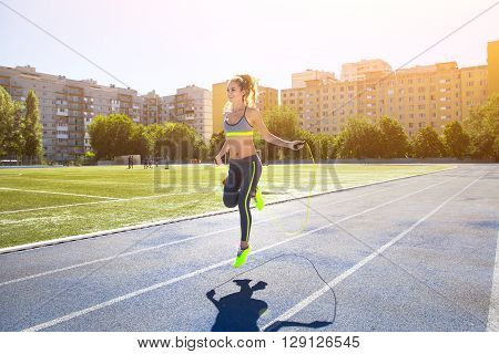 Woman with jumping rope. Beautiful young woman with a jumping rope in her hands with a stadium as background